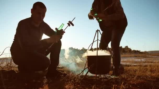 két turisták sör ül életmód, a tábortűz fél természet kemping silhouette napfény naplemente. két férfi megállt, Túrázás a napfény nyaralás üst fények a szabadban tüzet a motorháztető sziluett a