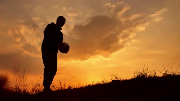 man coins a ball European the football soccer freestyle silhouette at sunset sunlight. man beats chasing ball football outdoors world championship lifestyle