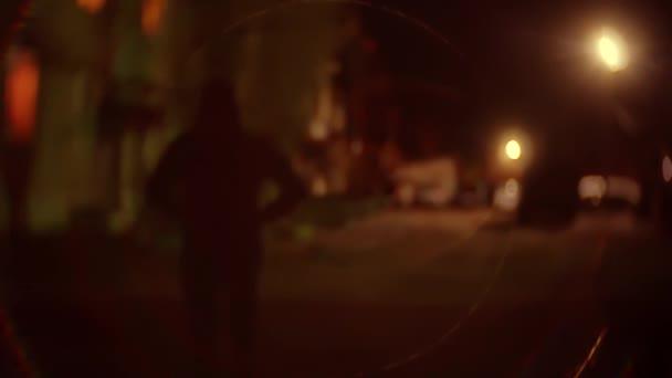 silueta lupič muž v kapuci je noční světlo lucerny zloděj pachatele. Neznámý lupič rozmazané pozadí jde bandita v kapuci lupič