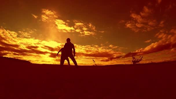 dva muži fotbal hráč hraje s míčem během západu slunce silueta zpomalené video venku. muži hraje Evropský fotbal na přírodě západ slunce silueta životní styl