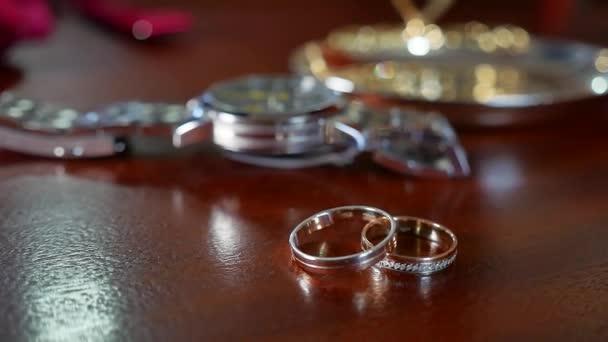 A mans a Zenske svatební prsteny. A mans Náramkové hodinky je v pozadí rozostřené.