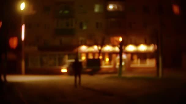 silueta lupič muž v kapuci je noční světlo lucerny zloděj pachatele. Neznámý lupič rozmazané pozadí venku jde bandita v kapuci lupič