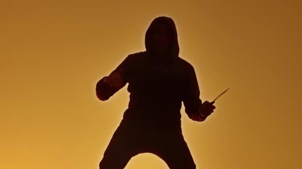 silueta muže v kápi s nožem. Životní styl stínu rozostření horor člověka v bundě s kapucí čelí skříňovou nástavbou a ukazují bandita nůž v ruce. Nebezpečný kriminálník s nůž vrah