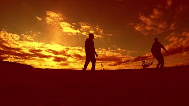 dva muži fotbal hráč hraje s míčem během západu slunce silueta zpomalené video. muži hrají venku Evropský fotbal na příroda západu slunce silueta životní styl