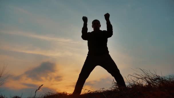 ember harcos harcművészeti szerzetes gyakorló silhouette karate kung-Fu a füves horizonton, naplementekor. Karate rúgás láb. Önvédelem művészete. Sziluettjét a háttérben drámai felhők: életmód