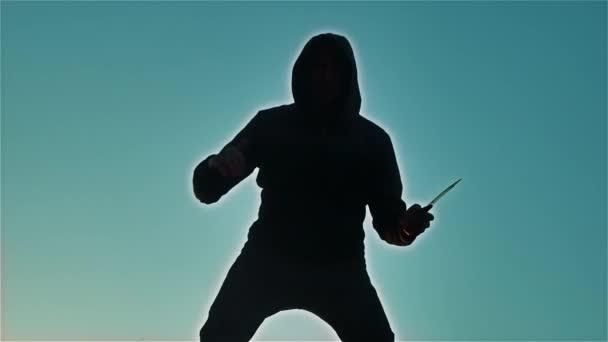 silueta muže v kápi s životní styl nůž. Stín rozostření horor člověka v bundě s kapucí čelí skříňovou nástavbou a ukazují bandita nůž v ruce. Nebezpečný kriminálník s nůž vrah