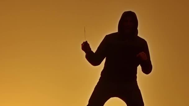 silueta muže v kápi s životním stylem nůž. Stín rozostření horor člověka v bundě s kapucí čelí skříňovou nástavbou a ukazují bandita nůž v ruce. Nebezpečný kriminálník s nůž vrah