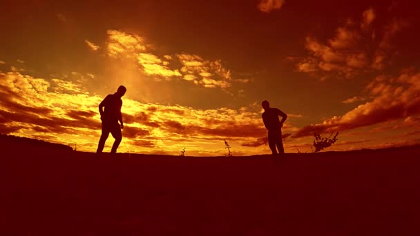 two man soccer player playing with ball during sunset silhouette slow motion video. men playing European soccer on nature outdoors sunset sunlight silhouette the lifestyle