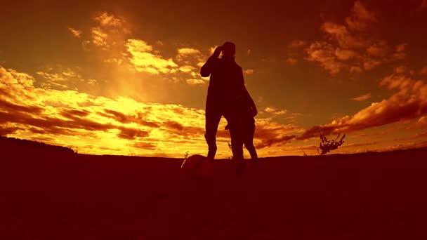dva muži fotbalista hraje s míčem venku slunce silueta zpomalené video. muži hraje Evropský fotbal na přírodě západ slunce silueta životní styl