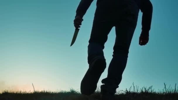 silueta muže v kápi s nožem. Stín rozostření horor člověka v bundě s kapucí proti straně životní styl tělo a ukazují nůž v ruce. bandita A nebezpečný kriminálník s nůž vrah