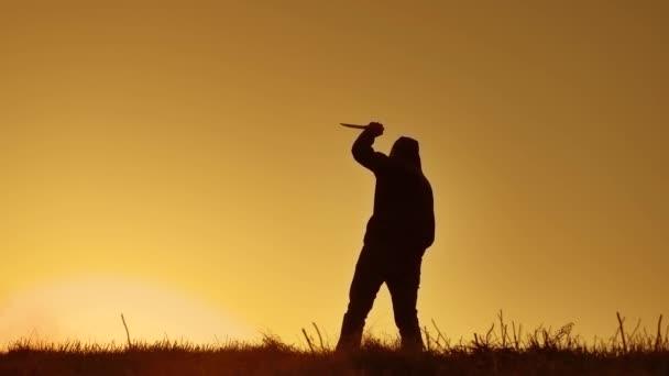 silueta muže v kápi s nožem. Stín rozostření horor člověka v bundě s kapucí proti straně životní styl tělo a ukazují bandita nůž v ruce. Nebezpečný kriminálník s nůž vrah