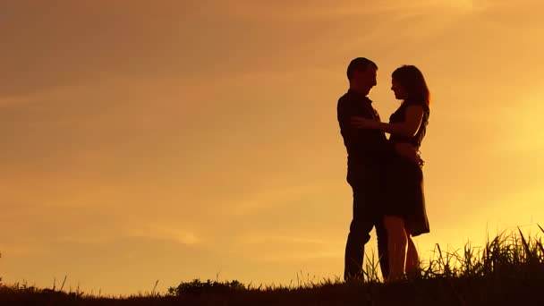 silhouette man circling girl amusement hugs at sunset. Man and woman silhouette in sunset slow motion. Couple in love kissing at sunrise. man and girl embrace silhouette lifestyle family concept