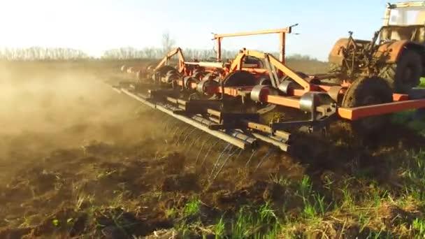 Farmář v traktoru půdě pluhy Rusko steadicam pohybu zemědělství pozemní příprava půdy s Záhonový kultivátor jako součást pre osazení aktivit v období Předjaří zemědělských prací na