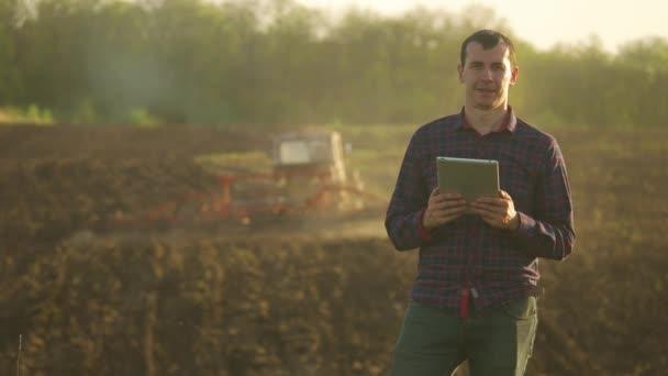 Uomo del coltivatore leggere o analisi un report in computer tablet su un campo di agricoltura con tono vintage su una luce del sole. il trattore ara un concetto di agricoltura di campo. Concetto di ecologia. Smart agricoltura utilizzando
