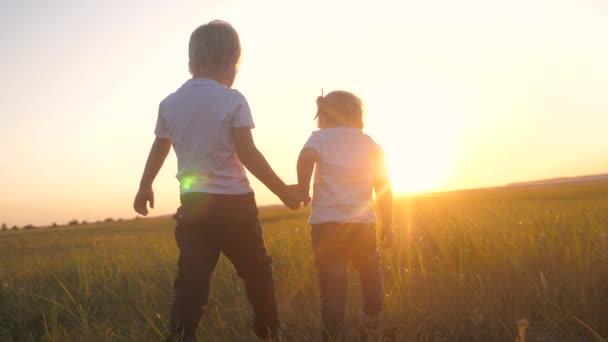 boldog családi csapatmunka testvér és testvér kéz a kézben sétálnak a parkban naplementekor a fűben. lassított felvétel kislány és fiú séta a természet életmód szabadban