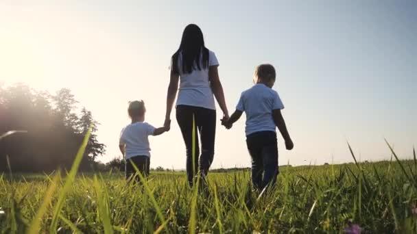 Šťastná rodina legrační chůzi jít za ruce týmová práce Silueta. šťastné děti malý chlapec a dívka s matkou rodiny při západu slunce. maminka a syn maminka dcera a syn v bílých tričkách chodit na