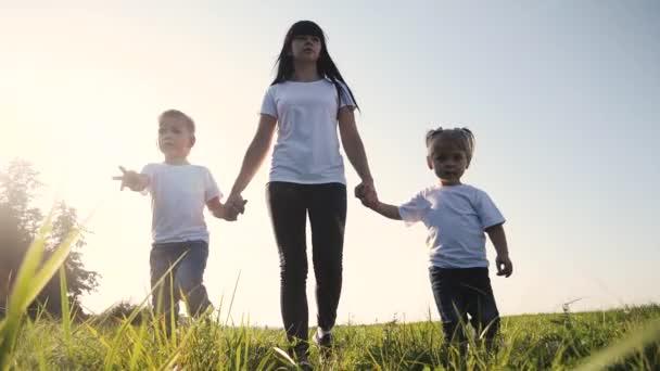 Šťastná rodina legrační chůzi jít za ruce týmová práce Silueta. šťastné děti malý chlapec a dívka s matkou rodiny při západu slunce. maminka a syn maminka dcera a syn životní styl v bílé trička
