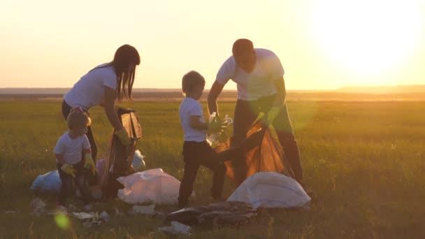 Umwelt Teamwork eine Ökologie Teamwork Silhouette Freiwillige Bewusstsein Umweltverschmutzung Haushalt Abfall Sonnenuntergang Zeitkonzept. Gruppe glückliche Familie von Menschen sammelt Müll Plastik und Papier Lebensstil Abfall