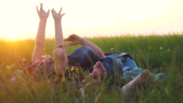 koncepce šťastných rodinných dětí. Děti s bosýma nohama ležet na trávě v parku na trávníku si odpočinout hrát bavte se. bratr a sestra přátelství bosé nohy relaxovat na trávě venku. malý chlapec a