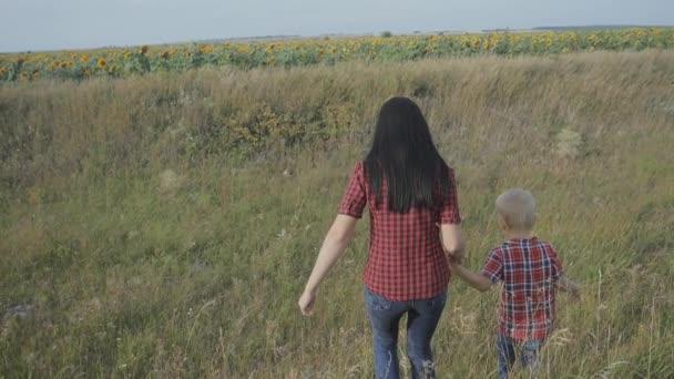 šťastná rodina máma a syn zpomalit video koncept. matka dívka a syn chlapec jít v přírodě na pole slunečnice životní styl. šťastná rodinná procházka v přírodě