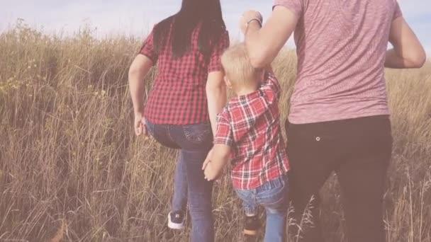 šťastná rodina máma, táta a syn kráčející zpomalené video koncepce. matka dívka, otec muž a syn chlapec jít v přírodě na pole slunečnic. šťastná rodina procházka životní styl v přírodě