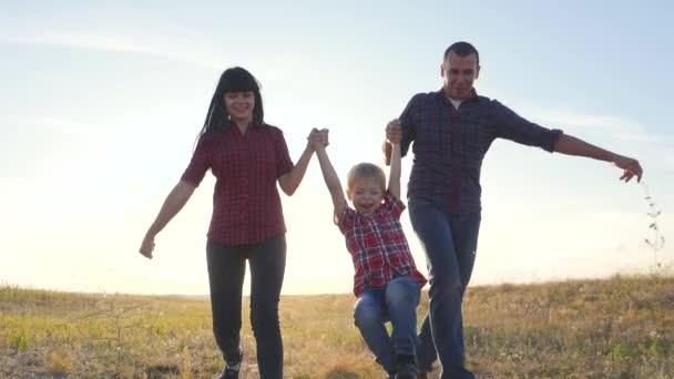 šťastný rodinný otec syn a máma běží zpomalit film zábavné video koncept. šťastný týmová práce táta muž maminka dívka a syn chlapec dítě běží držet ruce běh jít na životní styl pole v přírodě. bezstarostný šťastný