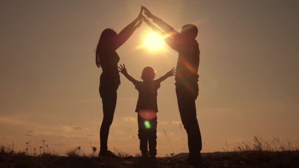 happy family teamwork silhouette shows a house and comfort symbol at sunset. mom dad and kids children portray a house lifestyle roof hold their hands over their heads