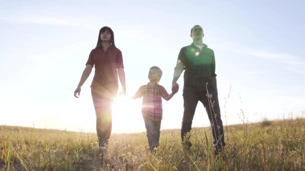 šťastný rodinný otec syn a máma jít zpomalit video koncept. šťastný týmová práce táta muž maminka dívka a syn chlapec dítě držet ruce životní styl chůze jít na pole v přírodě. šťastné rodinné bezstarostné dětství