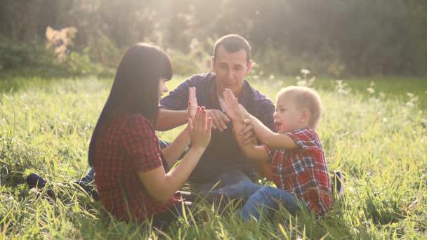 boldog család csapatmunka életmód kültéri koncepció szabadban lassított videó. anyu apa és egy fia a természetben ül a fűben szórakozni. játszik anyu lány apa és fia fiú boldog család