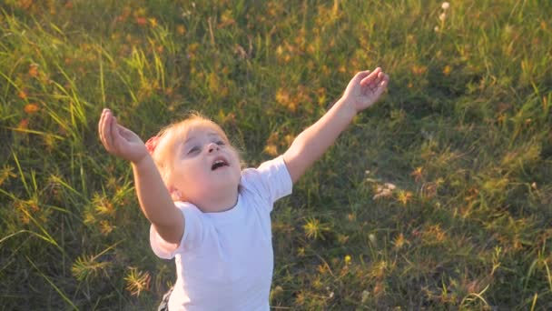 Malá holčička dětské ruce přitahuje do nebe koncept šťastné rodinné náboženství. Dcera zavřela oči a rozpřáhl paže na bok o přírodním životním stylu v parku při západu slunce.