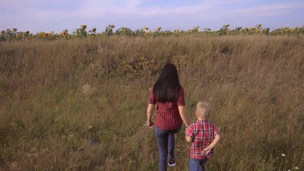 šťastná rodina máma a syn zpomalit video koncept. matka dívka a syn chlapec jít v přírodě na životní styl pole slunečnic. šťastná rodinná procházka v přírodě