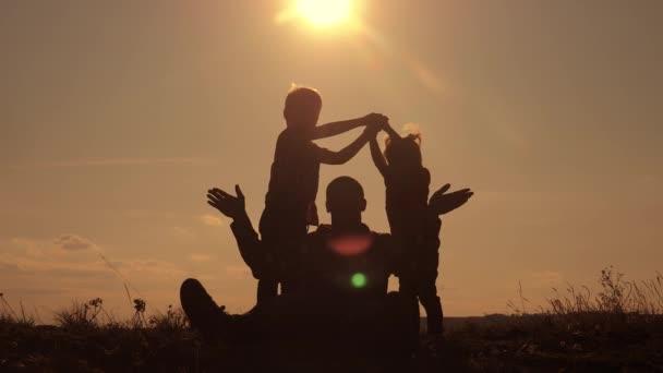 Die Silhouette der glücklichen Familie zeigt ein Haus und ein Symbol des Komforts bei Sonnenuntergang. Vater und Kinder zeigen ein Hausdach, das die Hände über dem Kopf hält.
