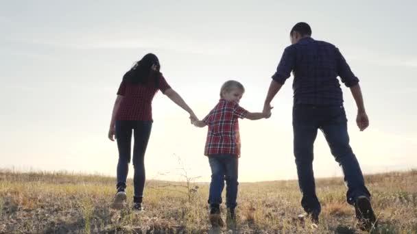 šťastný rodinný otec syn a matka jít pomalý životní styl video koncept. šťastný týmová práce táta muž maminka dívka a syn chlapec dítě držet ruce chůze jít na hřiště v přírodě. šťastné rodinné bezstarostné dětství