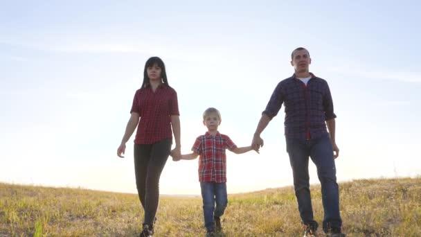 boldog család apa egy fiú és anya megy lassított videó koncepció. boldog csapatmunka apa férfi anya lány és fia fiú gyermek kéz a kézben járni a pályán a természetben. boldog család gondtalan életmód gyermekkor