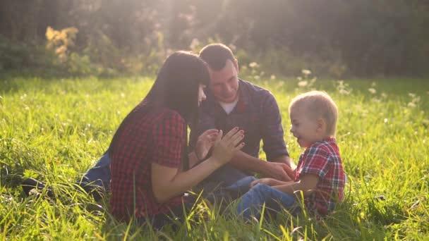 šťastná rodinná týmová práce venku koncept zpomalení videa venku. Máma táta a syn v přírodě sedí na trávě se bavit životní styl. hrát maminka dívka táta muž a syn chlapec šťastný rodina