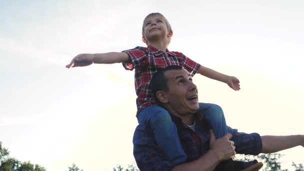šťastný rodinný otec syn koncept. Otec dává syn jezdit životní styl na zpět v přírodě venku.Portrét šťastného otce dávat syna jezdit na ramenou a dívat se nahoru. Roztomilý chlapec s tátou hraje