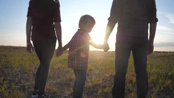 happy family concept a go. mom dad and son walk in the park at sunset field in nature. happy family man girl and little boy lifestyle slow motion video