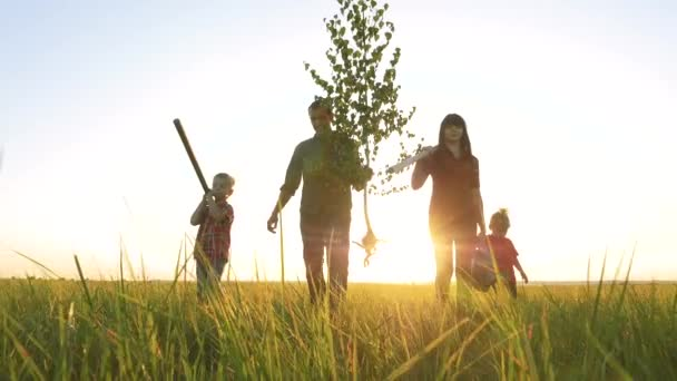 agriculture red neck farming happy family walking agriculture of farmers a silhouette concept slow motion video. lifestyle mom dad son and daughter walk go children happy family plant and water the