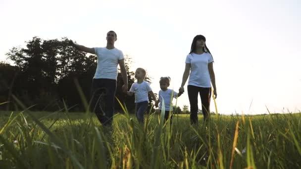 šťastná rodinná týmová práce tatínek maminka, mladší bratr a sestra procházka v parku příroda drží ruce zpomalené video koncept. otec maminka, děti chlapec a dívka dcera životní styl a syn držet za ruce jít na
