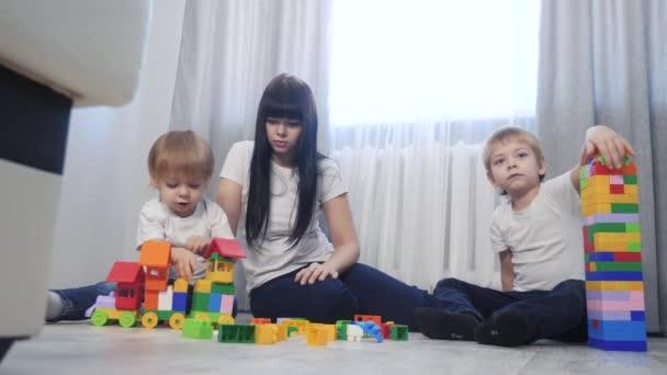 dětství šťastná rodina maminka a děti jsou životní styl hraje koncept holčička a chlapec bratr a sestra sbírá konstruktér týmová práce. dítě hraje hračky sedící na podlaze. děti si hrají v týmu