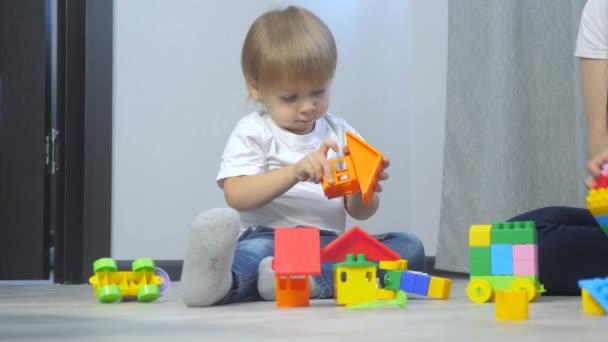 dětství šťastná rodina maminka a děti hrají životní styl pojetí holčička a chlapec bratr a sestra sbírá konstruktér týmová práce. dítě hraje hračky sedící na podlaze. děti hrají v týmu