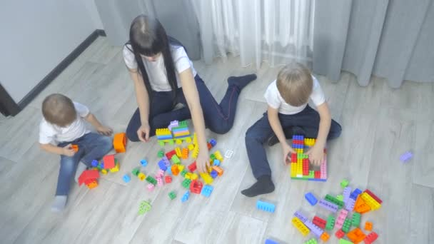 childhood happy family mom and children are playing concept little girl and boy brother lifestyle and sister collects constructor teamwork. child plays toys sitting floor. children play in team toys