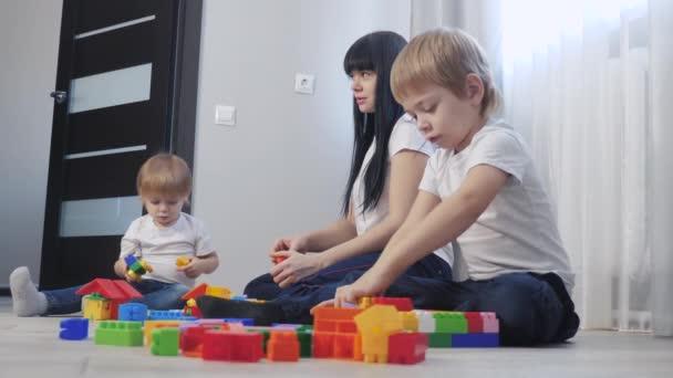 dětství šťastná rodina maminka a děti hrají koncept holčička a chlapec bratr a sestra sbírá konstruktér týmová práce. dítě hraje hračky sedící životní styl podlahy. děti hrají v týmových hračkách