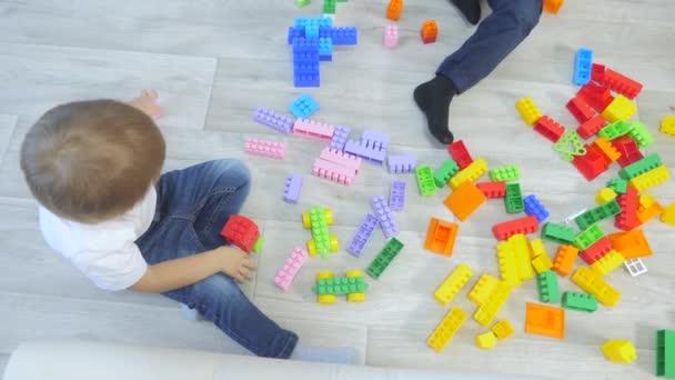 dětství šťastný rodinný koncept holčička a chlapec bratr a sestra sbírá konstruktér týmové práce životní styl. dítě si hraje s hračkami na podlaze. děti si hrají v týmu hraček na podlaze v místnosti