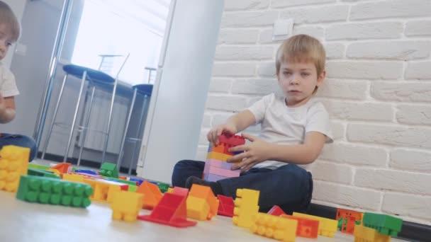 Dětství šťastný rodinný koncept holčička a chlapec bratr a sestra sbírá konstruktér týmová práce. dětský životní styl hraje hračky sedí na podlaze. děti si hrají v týmu hraček na podlaze v místnosti