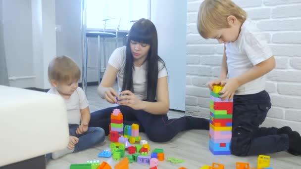 dětství šťastná rodina maminka a děti hrají koncept holčička a chlapec bratr a sestra sbírá konstruktér týmová práce. dítě hraje hračky sedící životní styl na podlaze. děti si hrají v týmu