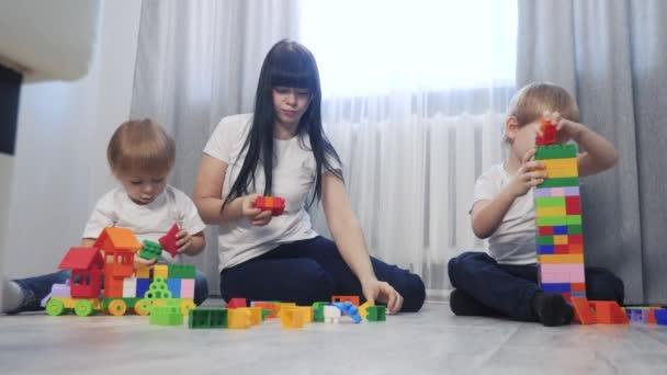 dětství šťastný rodinný životní styl maminka a děti hrají koncept holčička a chlapec bratr a sestra sbírá konstruktér týmová práce. dítě hraje hračky sedící na podlaze. děti si hrají v týmu