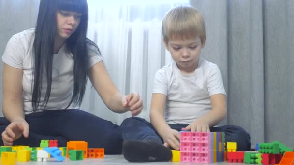 childhood happy family mom and children are playing concept little girl and boy brother and sister collects constructor teamwork. child plays toys sitting on lifestyle floor. children play in team