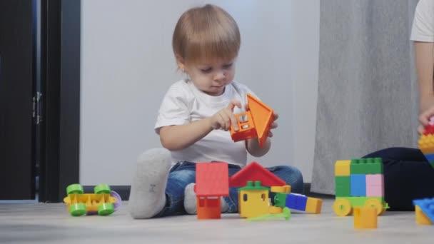 gyermekkori boldog család anya és gyerekek játszanak koncepció életmód kislány és fiú testvér és testvér gyűjti építész csapatmunka. A gyerek játékokat játszik a földön ülve. gyerekek játszanak a csapatban