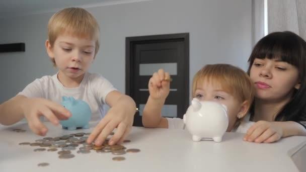 Šťastná rodina šetří peníze. Máma a děti dávají peníze do životního stylu v prasečí bance. holčička a chlapec dát mince v prasátko banky